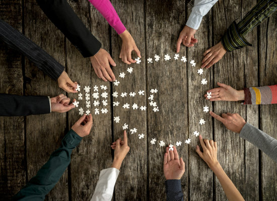 Teamwork and cooperation concept - group of twelve people, male and female, assembling a light bulb shape with blank puzzle pieces on a rustic textured desk, top view.