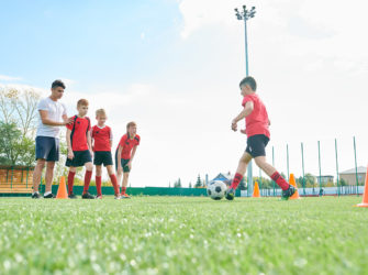 Side view portrait of junior football team training outdoors  with focus on  red haired boy leading ball between orange cones, copy space