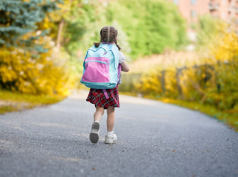 Pupil of primary school. Girl with backpack outdoors. Beginning of lessons. First day of fall.