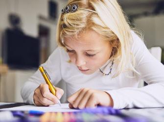 Cute girl writing her homework for elementary school at home.