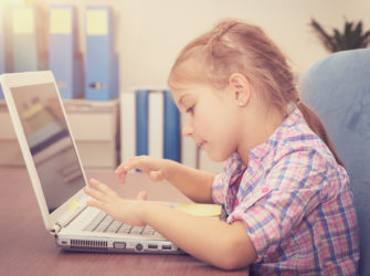 Little girl working on the laptop at home, sweet schoolgirl doing homework using wireless internet, typing on the computer, back to school concept